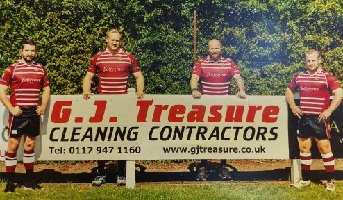 Photo of Cleve Rugby Club Players stood in front of G J Treasure sponsor advertising board